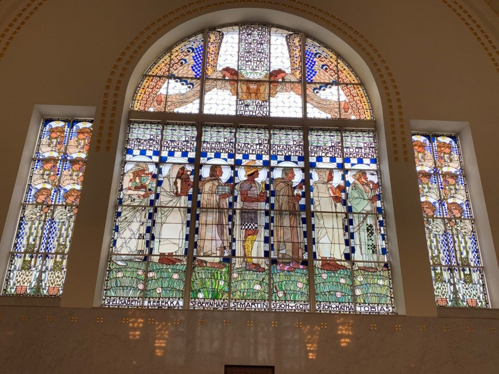 Window at St. Leopold's Church, depicting the seven corporal works of mercy. Photograph by Margaret S. Chisolm